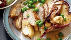 Apple-stuffed roast chicken with cider and pea sauce