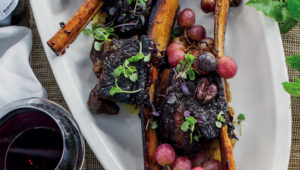 Sticky beef ribs with grapes and olives